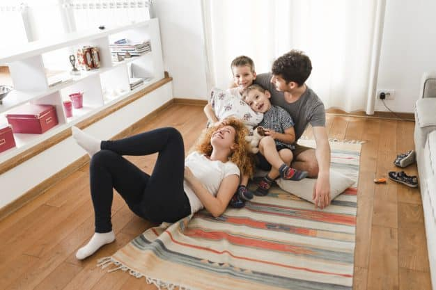 inside tiny houses - Happy family hanging out in living room