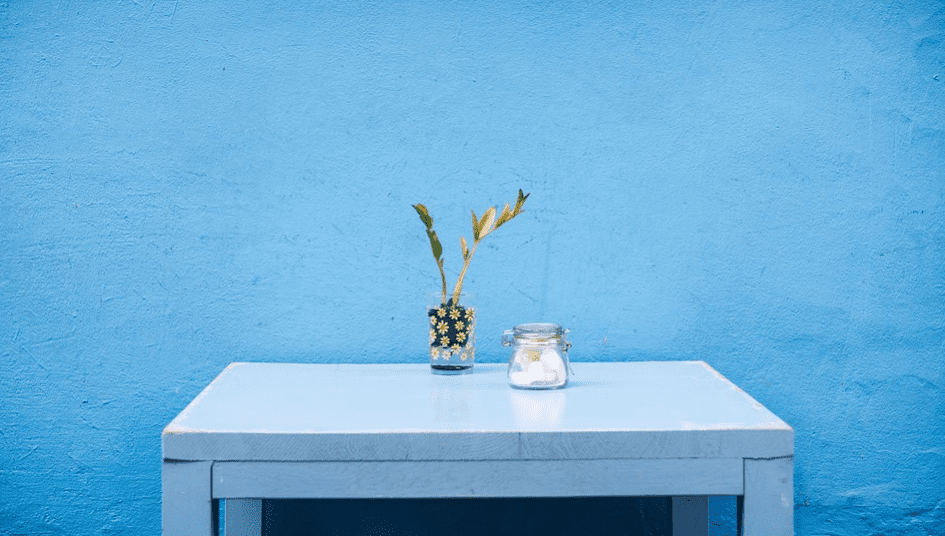 flower vase and glass jar at the top of white table against blue wall